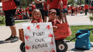 """But... What is a """"Fully-Funded"""" School? Kids holding posters Fund our future."""
